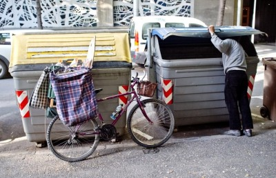 A man searches through trash bins in Girona, Spain. Across Spain, people are increasingly dumpster diving for scraps of food or metal. (Courtesy of Richard van der AA/Demotix/Corbis)