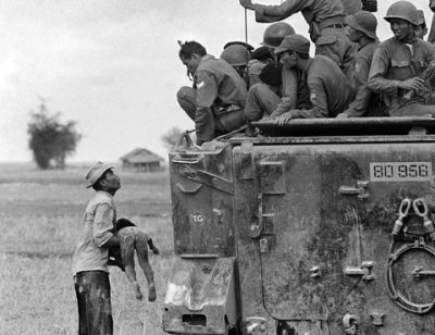 Horst Faas/Associated Press A farmer helplessly holds the body of his dead child as South Vietnamese troops look on, March 19, 1964. The child was killed as government forces pursued guerrillas into a village near the Cambodian border.