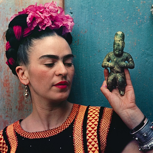 Frida holding an Olmec figurine at her home, La Casa Azul, in 1939. Photo by Nickolas Muray.