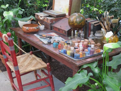 A reimagine corner from Frida's studio features her desk, brushes and paint pots.