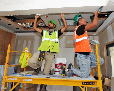 Mohammad Alsharif (left) and Christian Plaza of the New York City College of Technology apply drywall mud on Day 9 of the U.S. Department of Energy Solar Decathlon at the Orange County Great Park, Irvine, California Tuesday, Oct. 6, 2015. (Credit: Thomas Kelsey/U.S. Department of Energy Solar Decathlon)