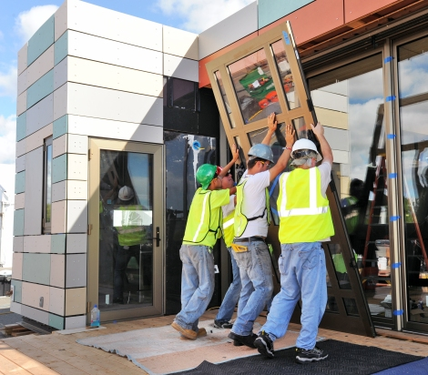 Team members of Crowder College and Drury University install Hurricane resistant shield doors to withstand 200 mph winds on Day 8 of the U.S. Department of Energy Solar Decathlon at the Orange County Great Park, Irvine, California Monday, Oct. 5, 2015. (Credit: Thomas Kelsey/U.S. Department of