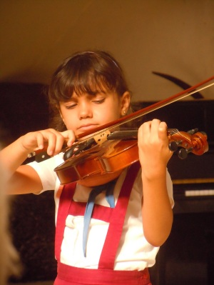 An aspiring musician learns violin at music school