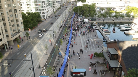 A small section of the 650 metre ribbon passing through the crowd gathered at the 650-meter Simcoe Wave Deck. Photo credit CNW