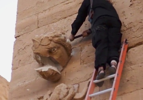 In this image made from a militant video posted on YouTube on Friday, April 3, 2015, which has been verified and is consistent with other AP reporting, a piece falls off from a curved face on the wall of an ancient building as a militant hammers it in Hatra, a large fortified city recognized as a UNESCO World Heritage site, 110 kilometers (68 miles) southwest of Mosul, Iraq. (AP Photo/Militant video) NYTCREDIT: Uncredited/Militant video, via Associated Press
