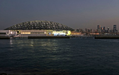 In this Monday, Nov. 6, 2017, photo, the night view of Louvre Abhu Dhabi is seen in front of the city skyline in Abu Dhabi, United Arab Emirates. The Louvre Abu Dhabi is protected a massive 7,500-ton dome stretching 180 meters (590 feet) across, but it lets the world in. The Louvre Abu Dhabi is preparing its grand opening _ unveiling its treasures to the world after a decade-long wait and questions over laborers' rights. The museum, which opens on Saturday to the public, encompasses work from both the East and West. (AP Photo/Kamran Jebreili)