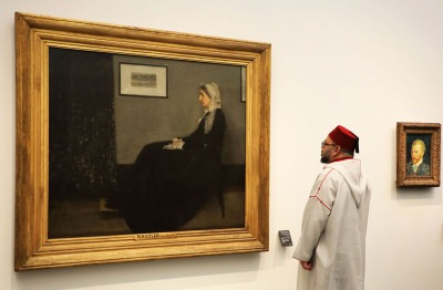 "Moroccan King Mohammed VI looks at the iconic painting ""Whistler's Mother"" by James Abbott McNeill Whistler (1871) as he visits the Louvre Abu Dhabi Museum during its inauguration on November 8, 2017. Photo by Ludovic Marin/Agence France Presse."